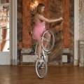 Woman performs ballet routine with a bicycle